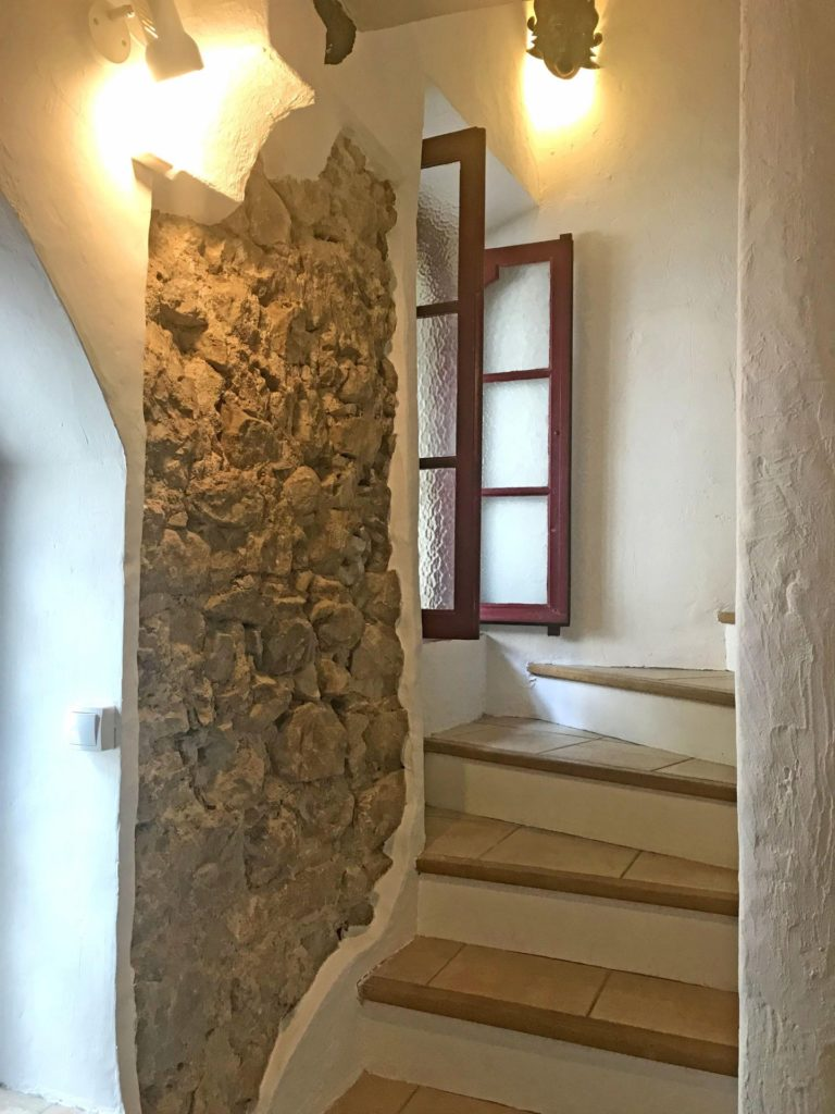 stairway of vence property with exposed pebbled stone wall with open window