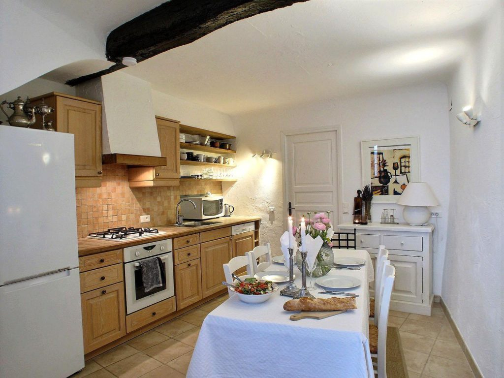 kitchen interior with table in center with white table cloth and wooden cabinets