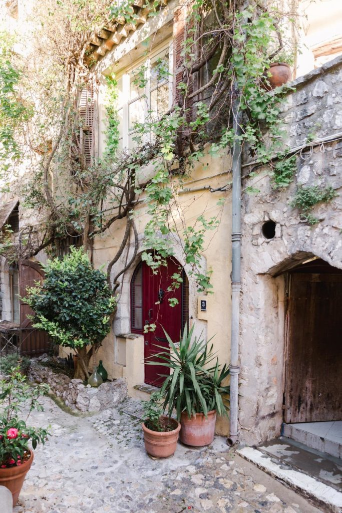 entrance to village house in vence with yellow walls and big red door