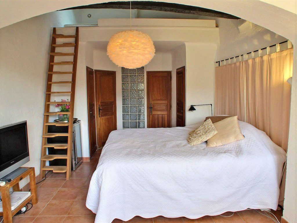 bedroom of village house with ladder to lofted area