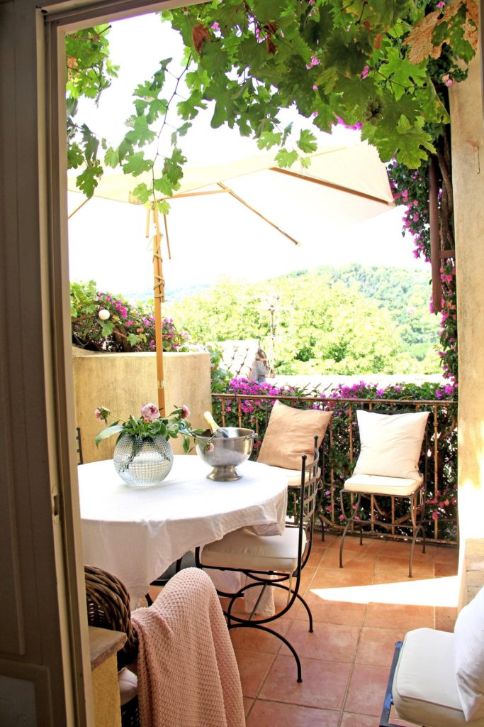 outdoor table with white tablecloth with overhead large umbrella