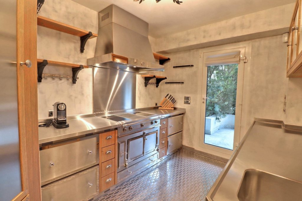kitchen in cannes croisette apartment for sale with silver appliances and wood shelves