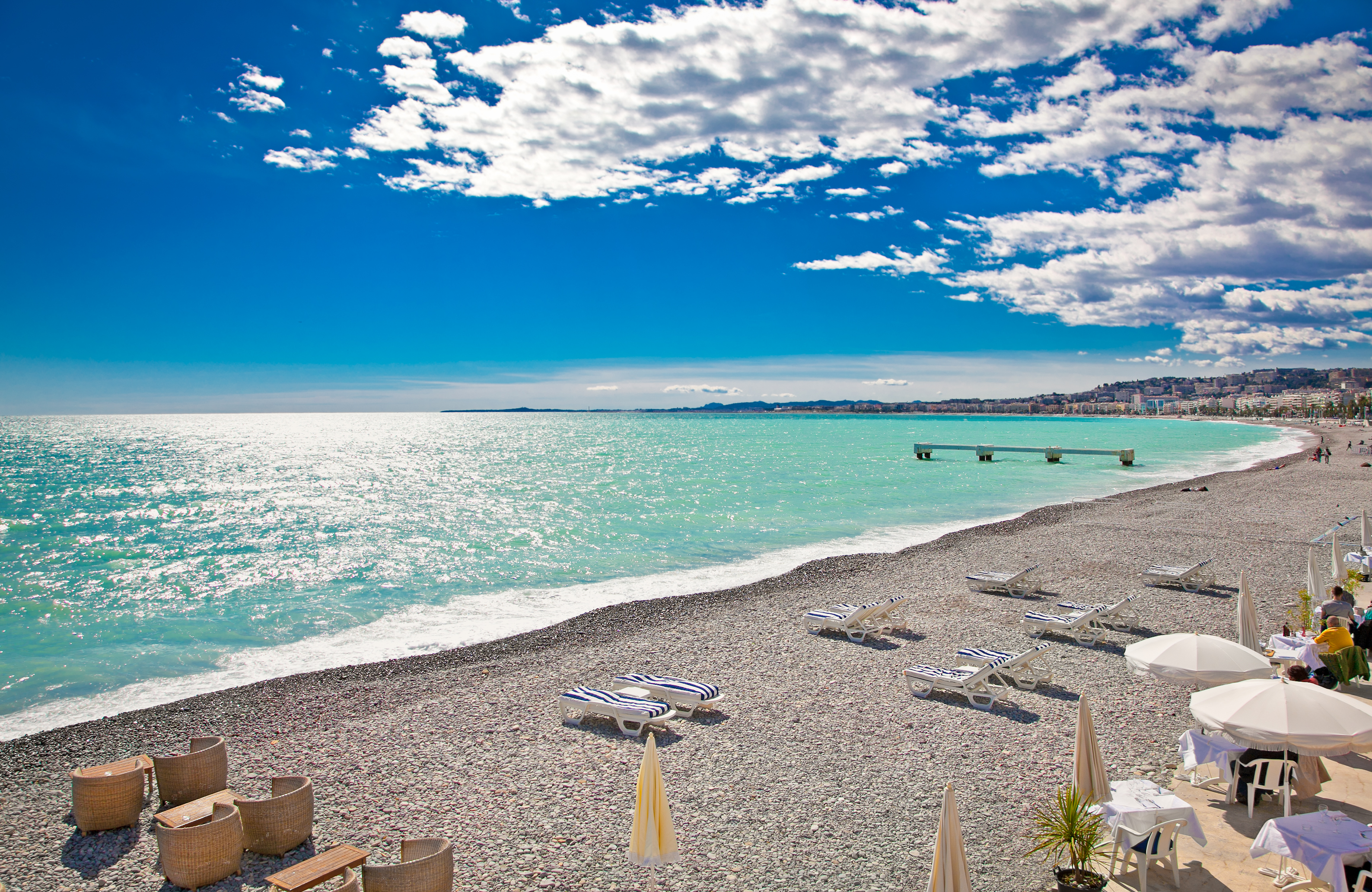rocky beach of Nice, South of France. Bright blue water and blue sky.