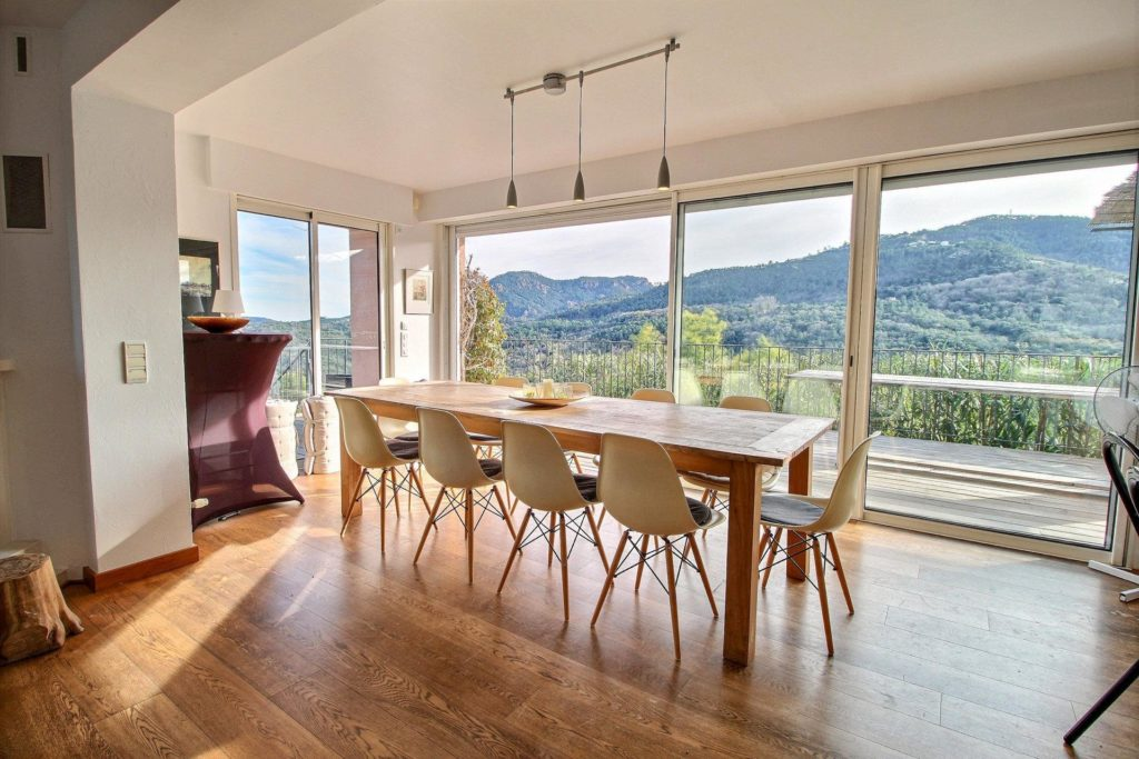 dining room area with floor to ceiling windows and balcony access