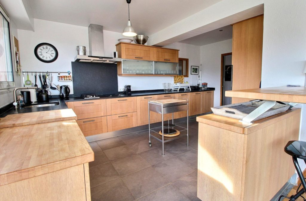 modern kitchen with light wood cabinets and dark steel appliancesw and tile floors