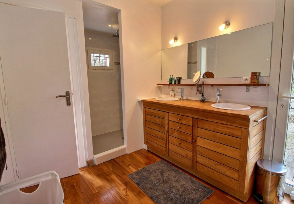 bathroom with light wood cabinets and cream walls