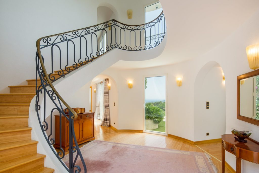stairway with metal railing and white walls with wood floors