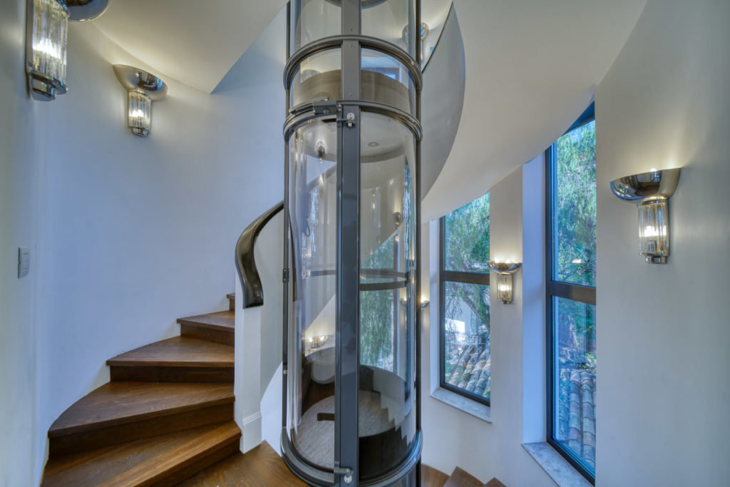 stairway of luxury home with modern elevator in center