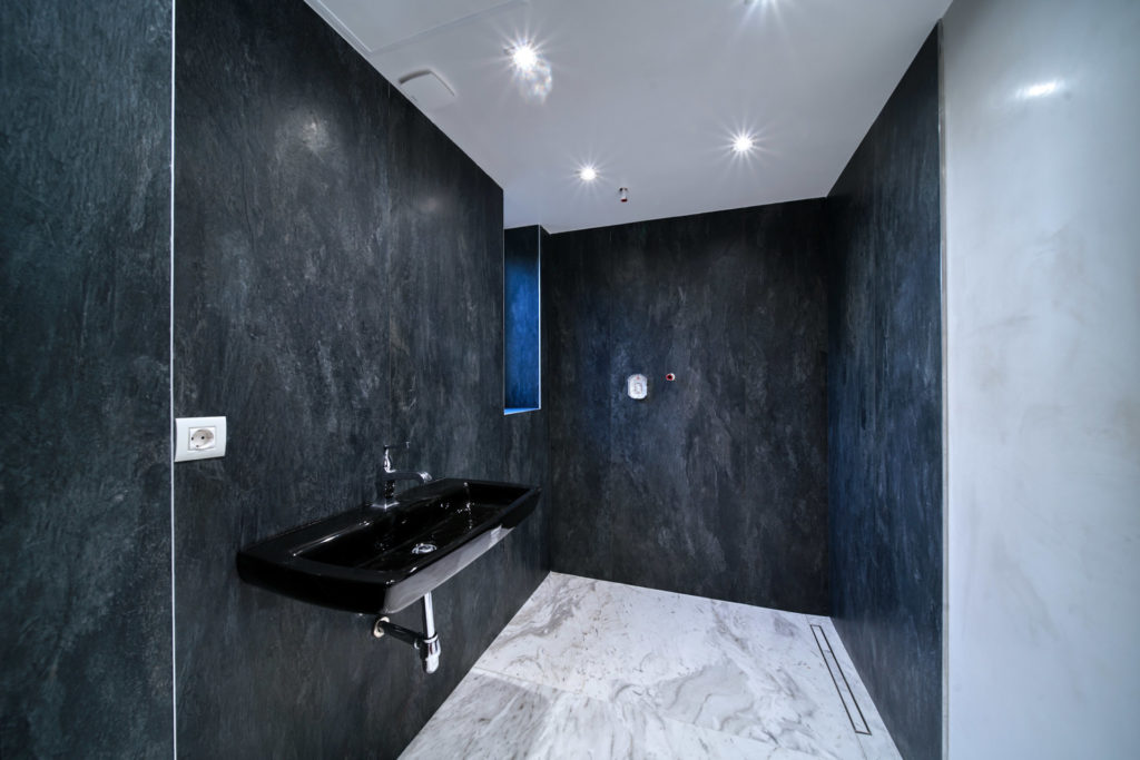 modern bathroom with dark tile walls and white marble walls