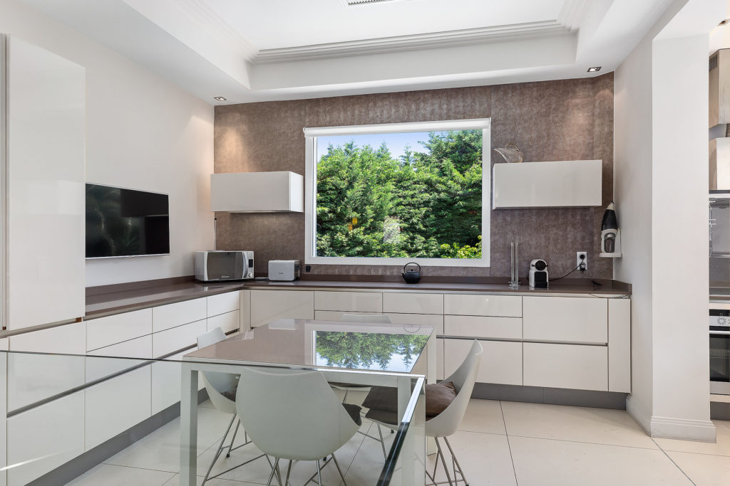 kitchen with grey wall and white cabinets with center glass table