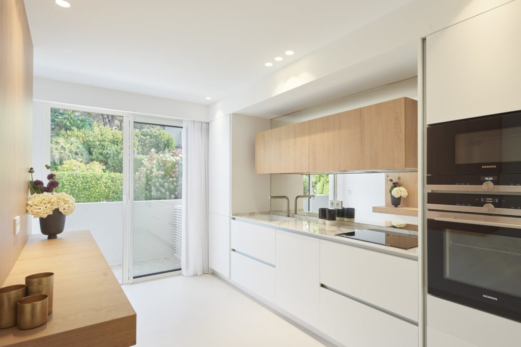 modern kitchen with white counters and wooden cabinets in cannes apartment for sale