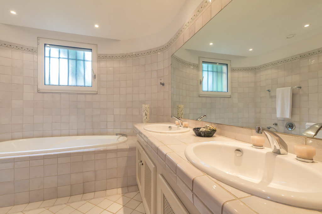 all white bathroom with bath tub and large rectangular mirror