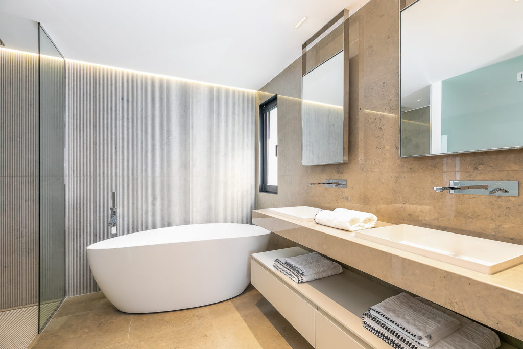 modern bathroom with large white bathtub and double sink