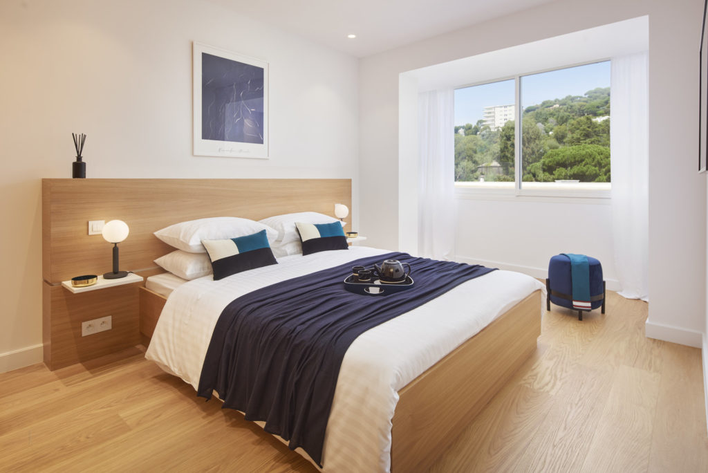 bedroom with small window and navy and white bedroom
