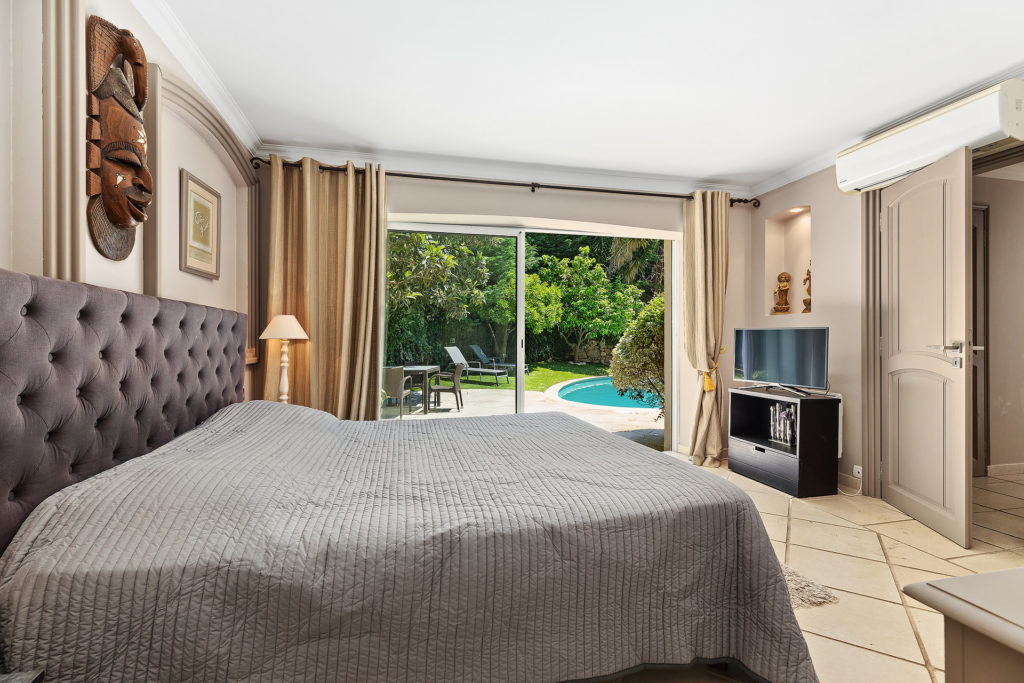 modern style bedroom with grey bed and padded bed head with slidding door access to backyard pool and garden