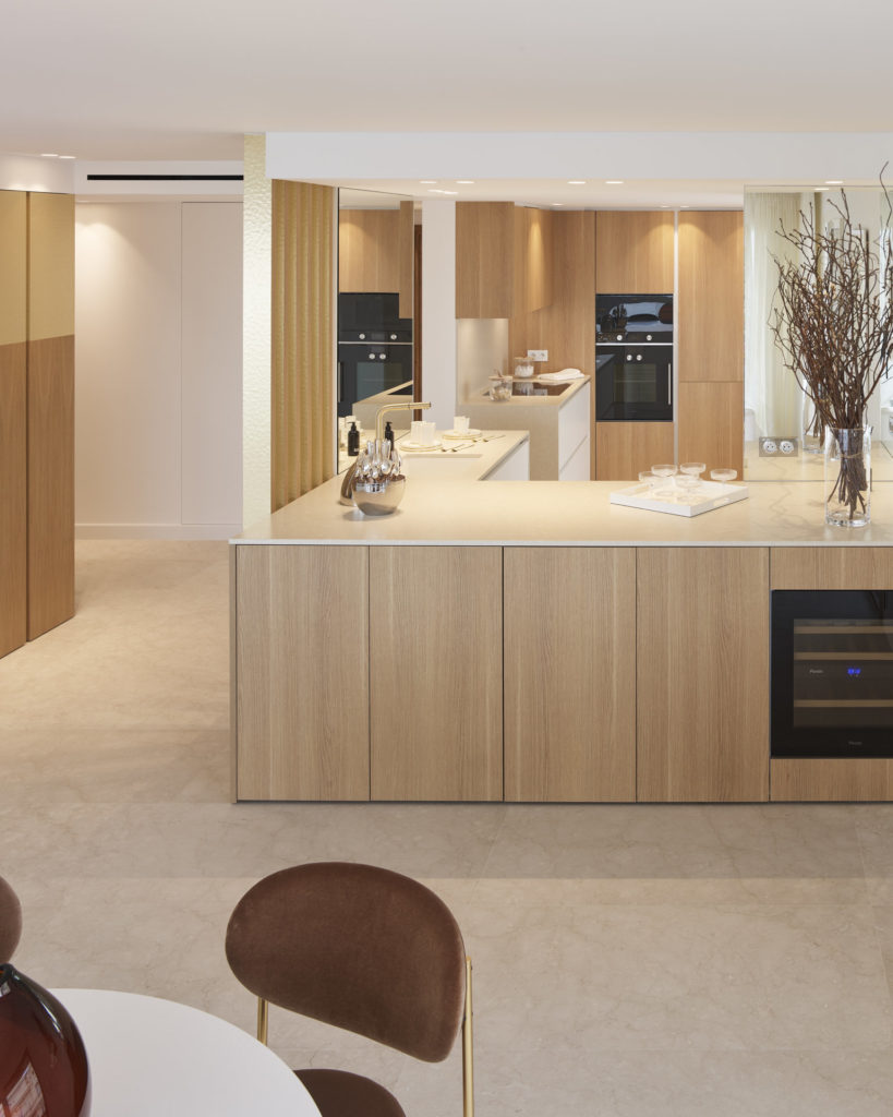 modern kitchen with light wood cabinets and matte black appliances