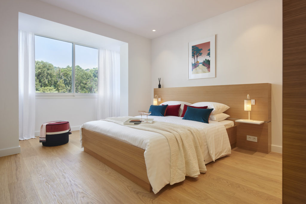 bedroom of luxury property in cannes californie with light wood floors and white bedding