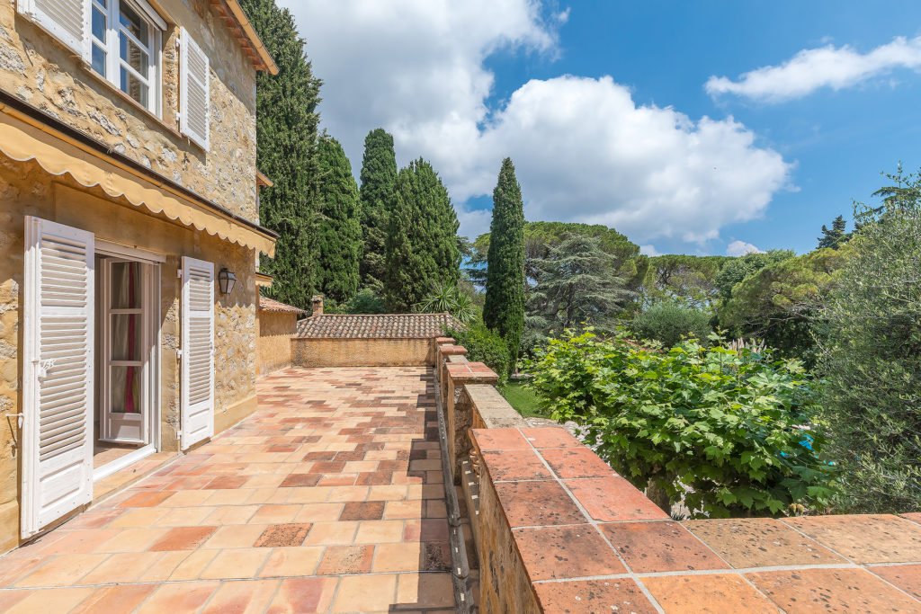 top floor balcony with checkered tile floors and view of tall trees blue sky with large white clouds