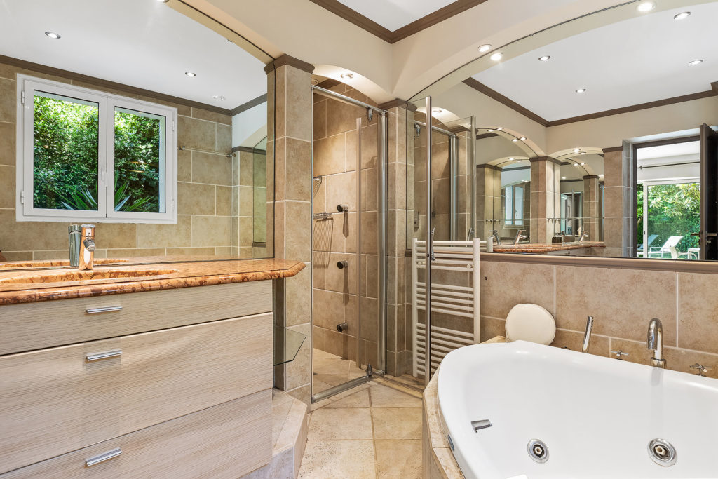 bathroom of holiday home south france with bathtub and shower and grey tile