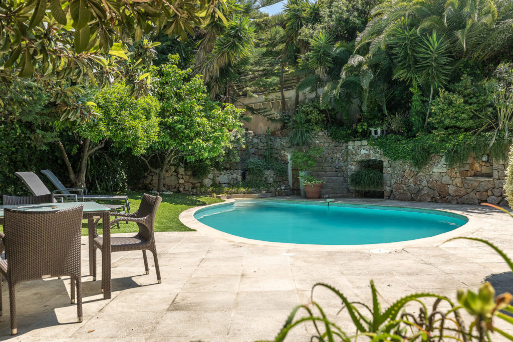 backyard of villa property with large private pool and garden
