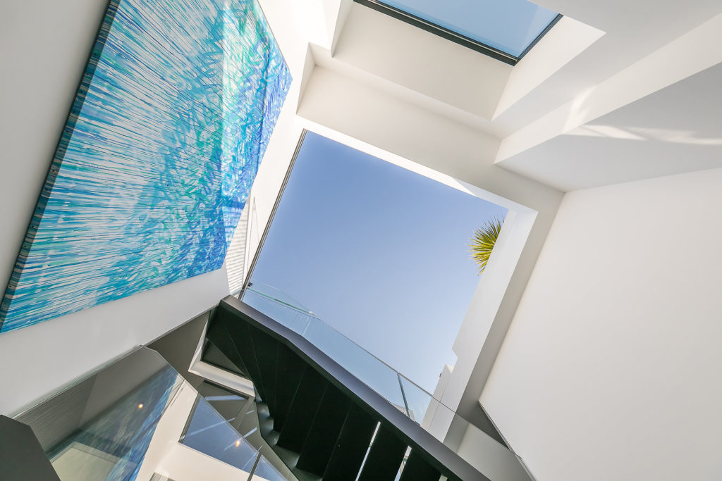 stairway with open top ceiling sky view and large blue painting modern property in south france