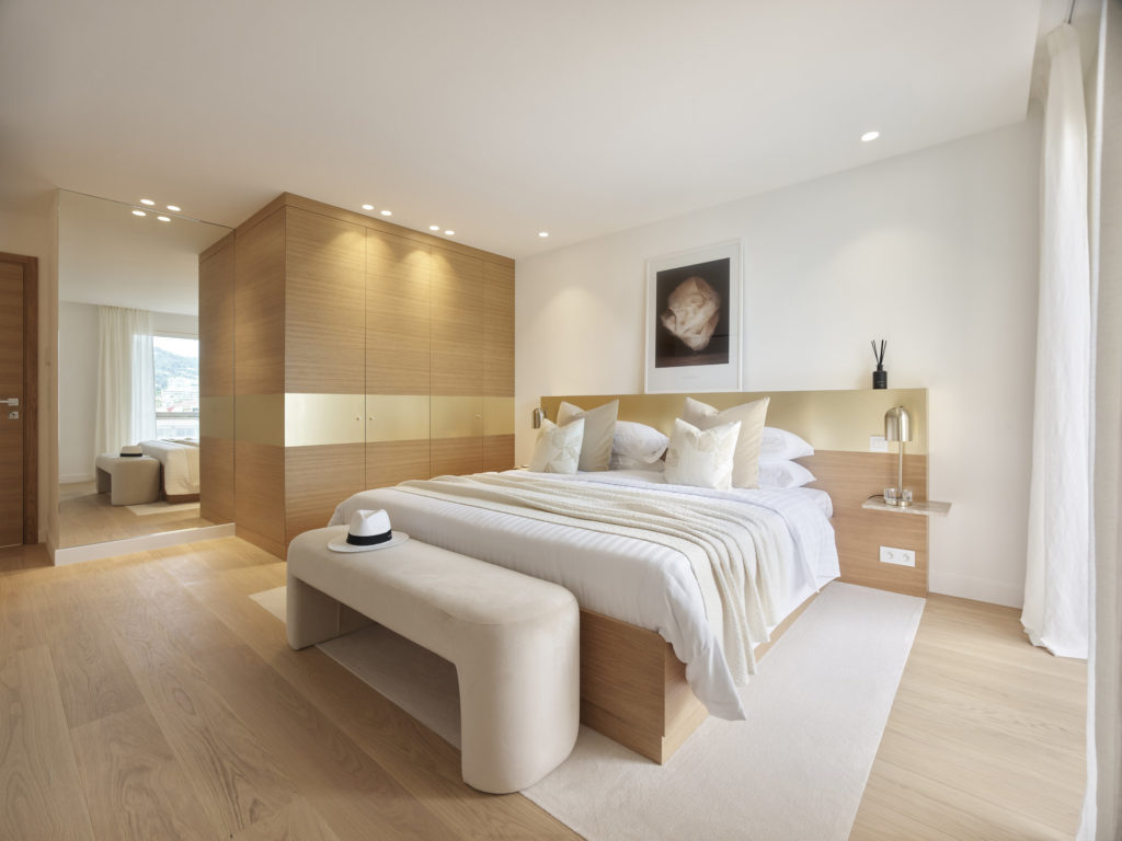 bedroom with queen size fluffy bed and light wood floors and simple modern aesthetic