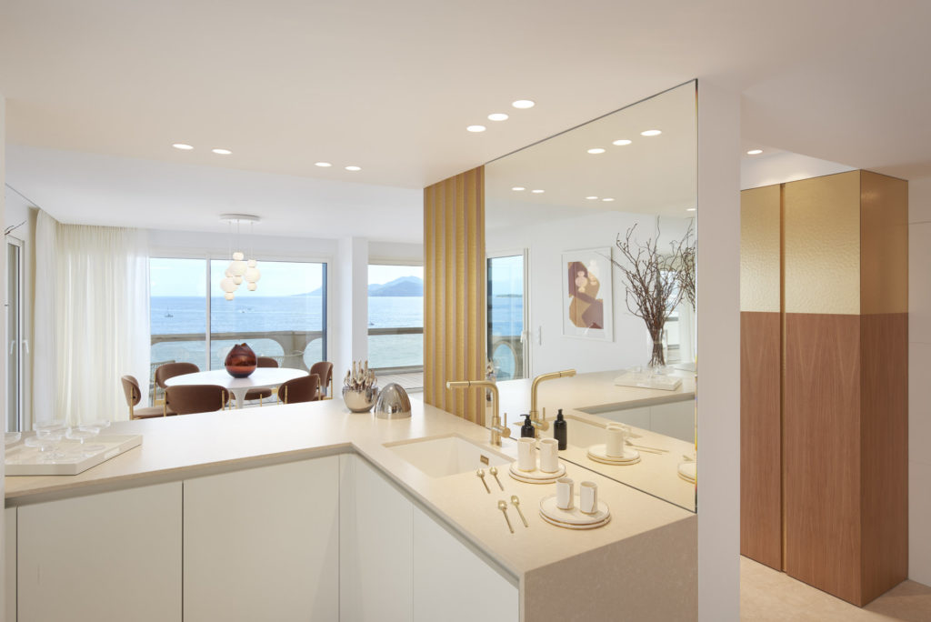 kitchen with white marble counter top with white cabinets and open view to living and dinning area