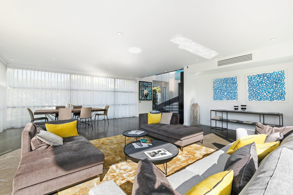 living room with modern design with white backdrop and grey couch south france