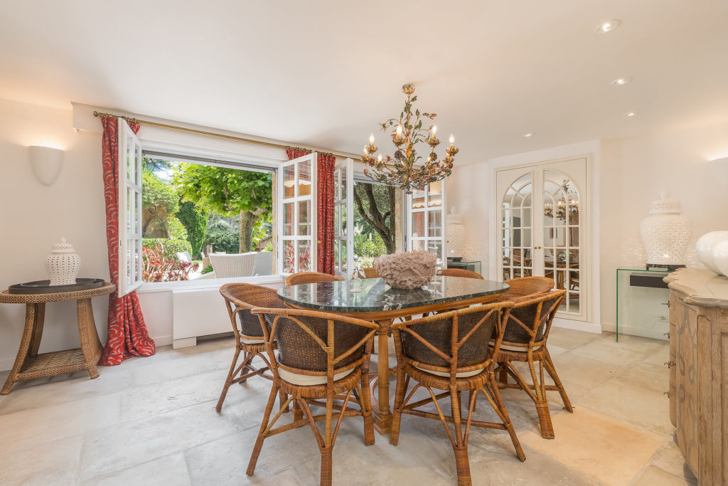 dining table that is wood and ceiling chandelier with open windows to backyard