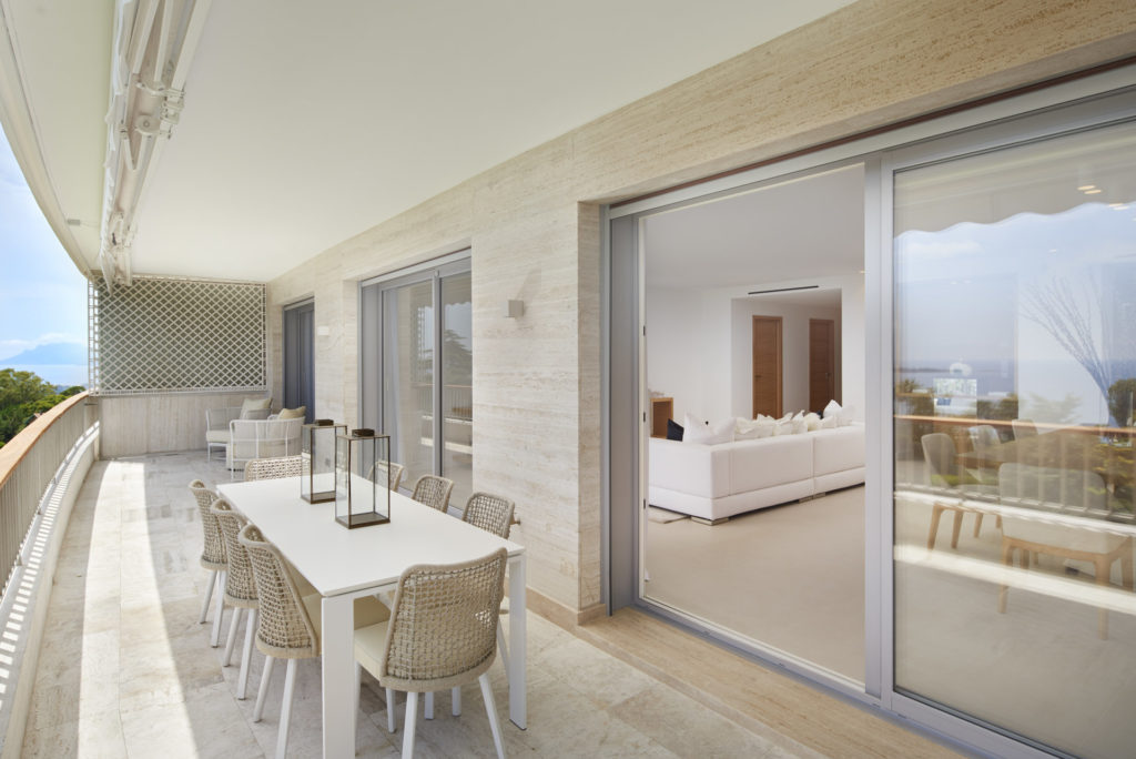 terrace of apartment in cannes with white table and glass door access to living room