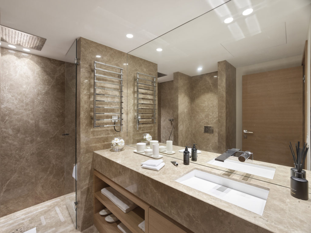 bathroom with grey tone wood accents and double sink with standing shower