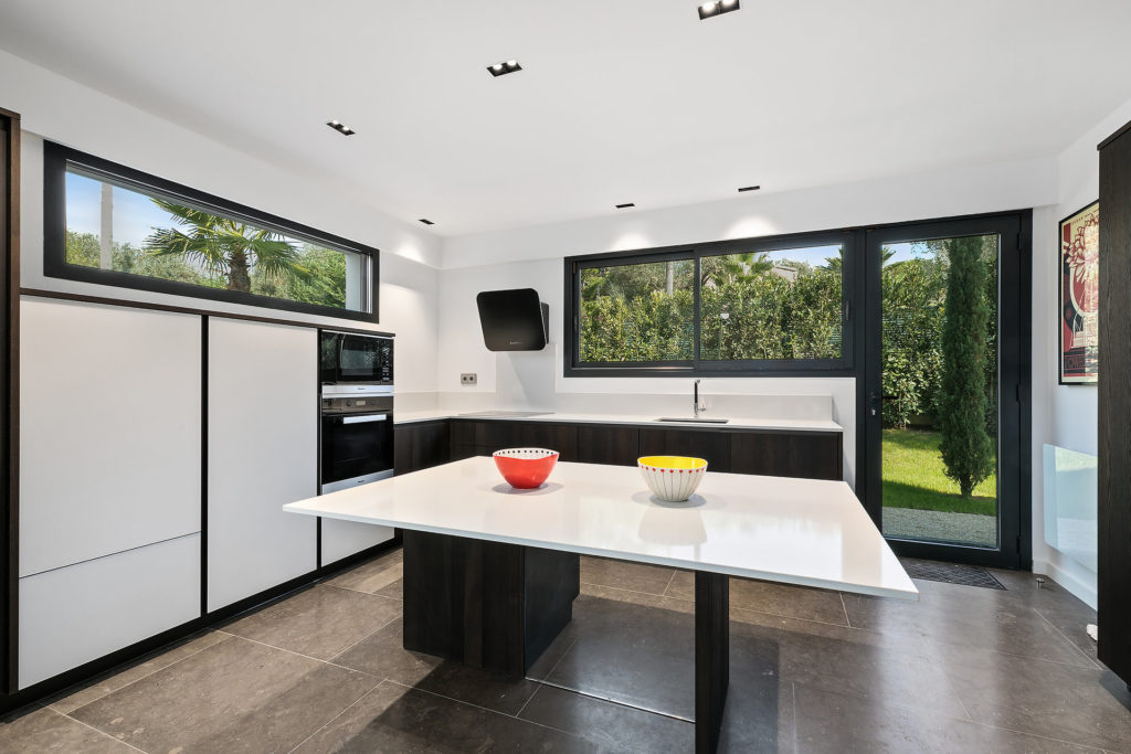 modern kitchen with white large center island and dark cabinets with white counter tops