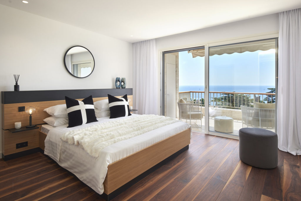bedroom with wood floors and queen size bed with sliding glass doors to terrace