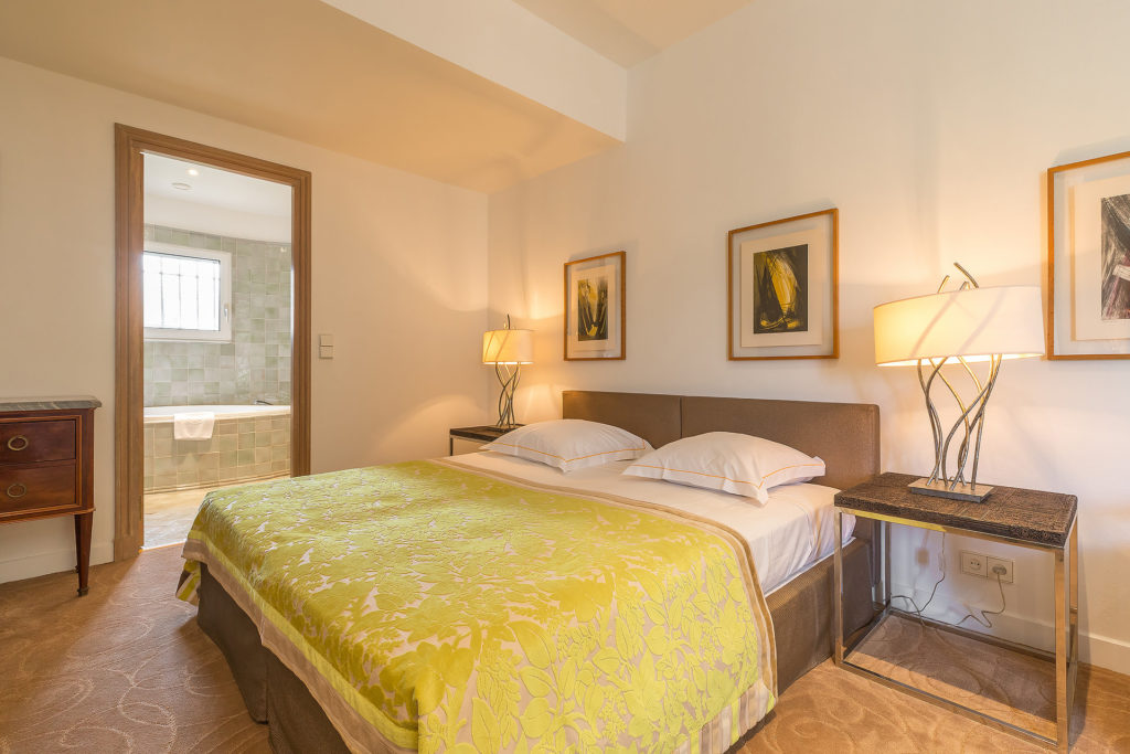 bedroom of house in south of france with yellow bedding and classic paintings above bed frame