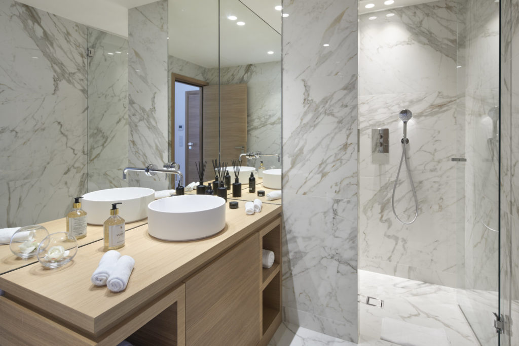 bathroom with marble floors and walls and light wood counters