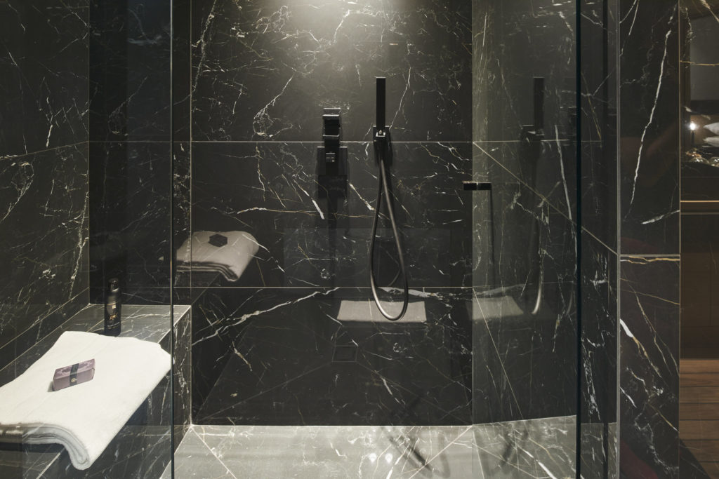 shower of bathroom with black marble at luxury property in cannes