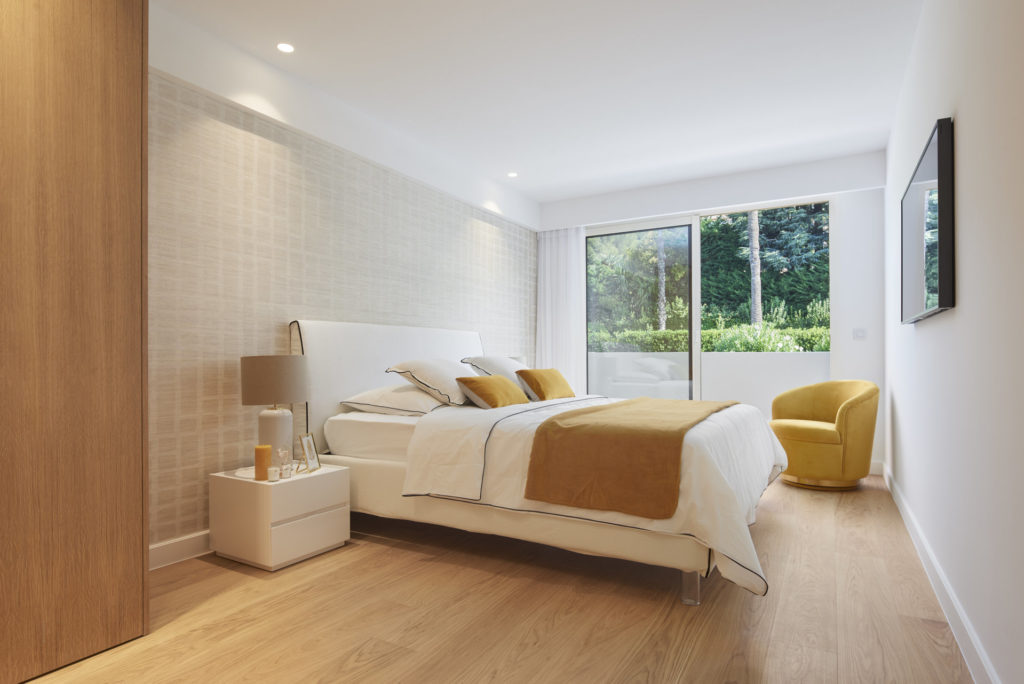 modern bedroom of apartment in cannes with wood floors and large windows