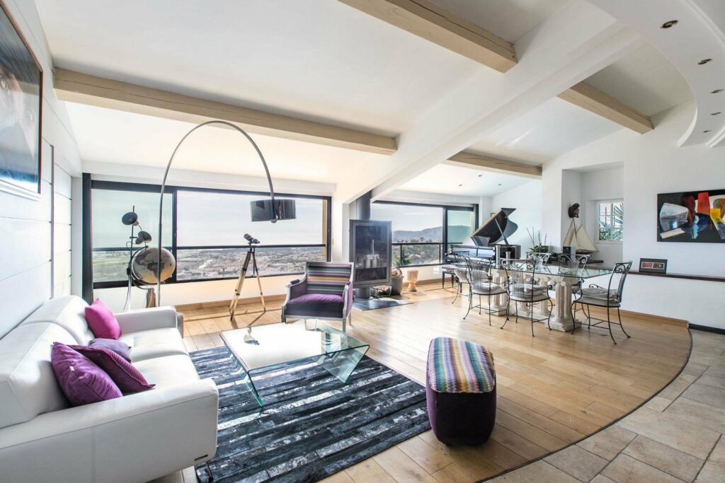 modern luxury villa in mougins with leather couch and retro style lamp with sliding doors leading to balcony