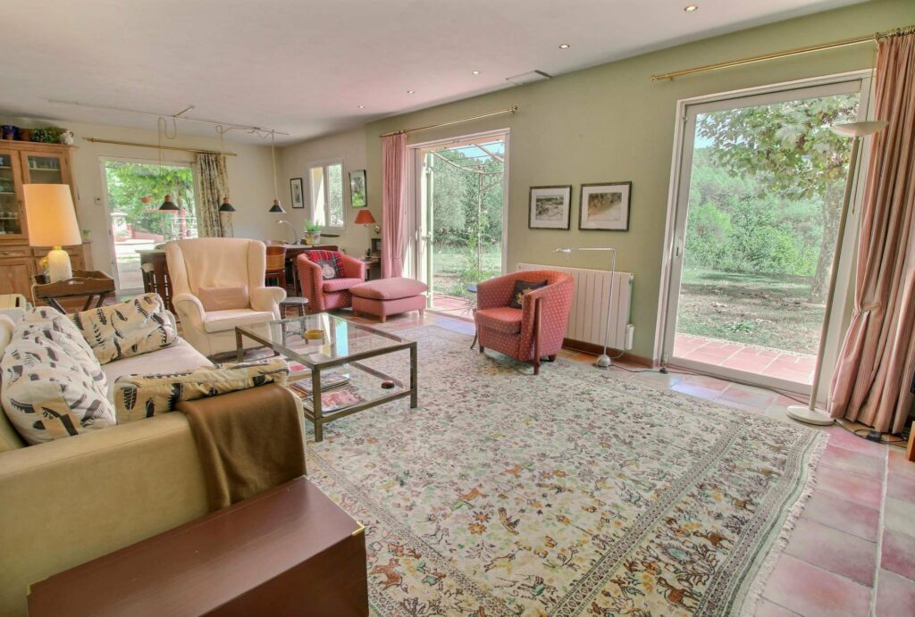 charming villa living room with patern rug and red accent chairs and large windows gardeb view