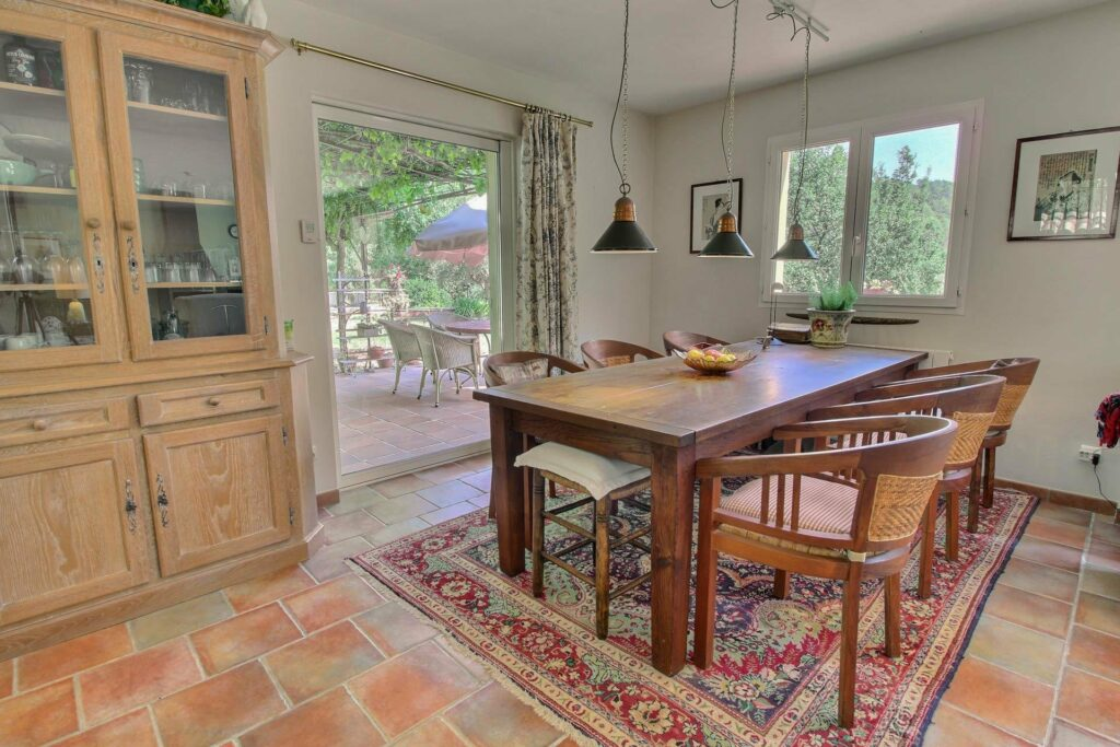 square wooden dining table with pattern rug underneath next to sliding door to backyard