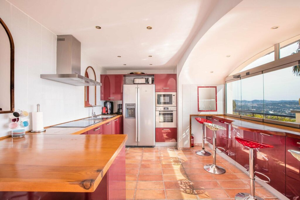 retro style kitchen with tile floors with red walls and wooden varnished counter top