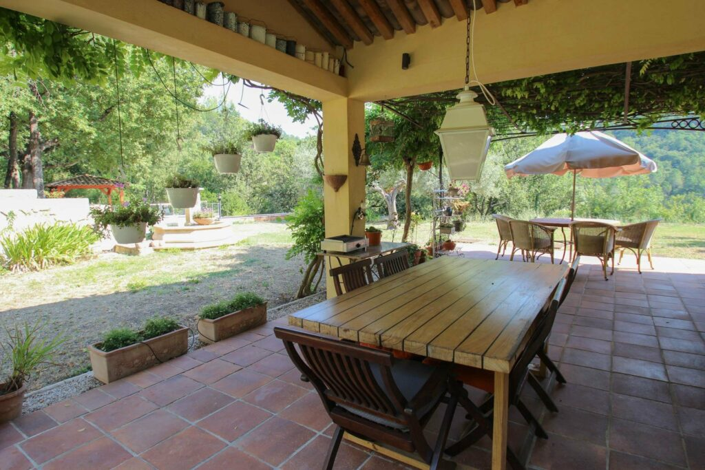 large backyard of property with outdoor table and provencal decor rustic tiled floors