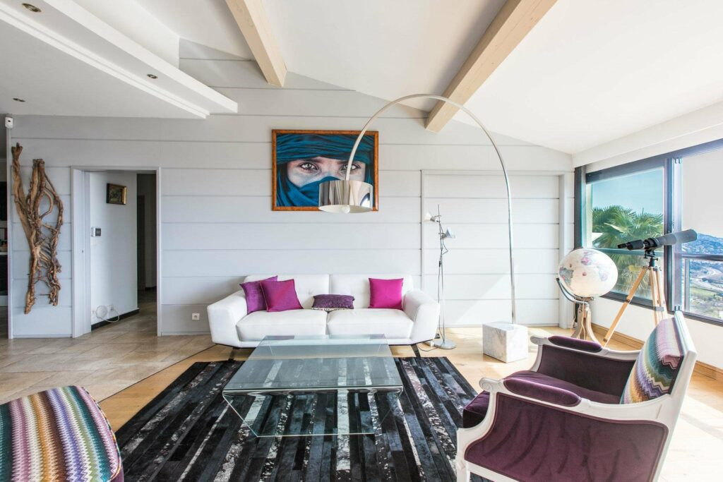 living room with white modern couch and exposed light wood beams and printed dark blue rug