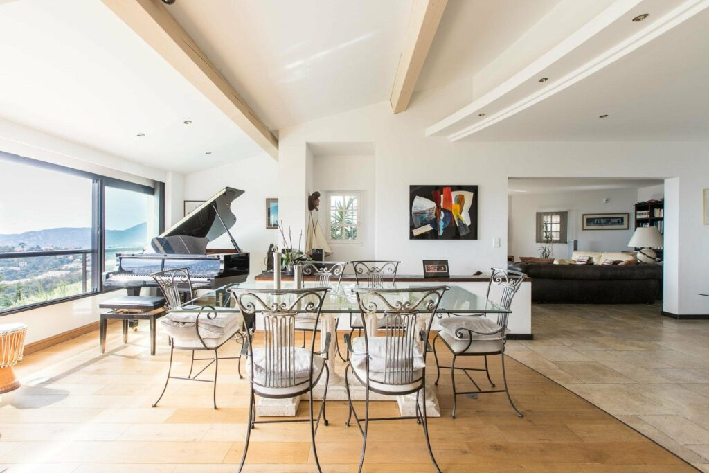 dining room with large glass table and grand piano in corner