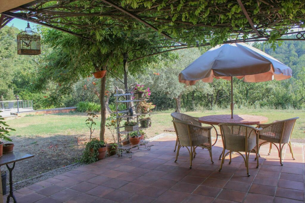 outdoor furniture with table and umbrella in outdoor garden holiday home
