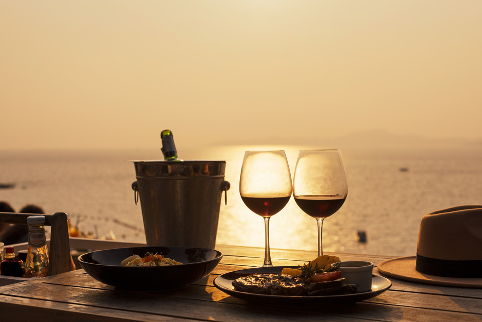 view of two glasses of wine on a table with sun setting in the background in French Riviera