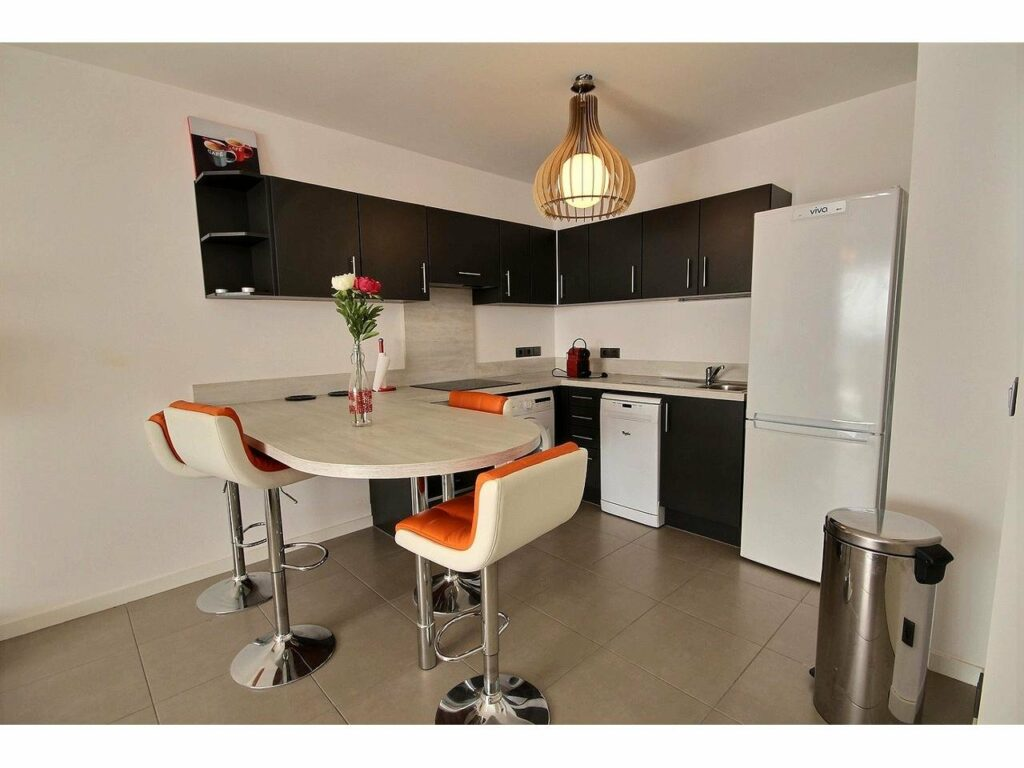 kitchen with white appliances and dark wood cabinets and center round table with orange cushion