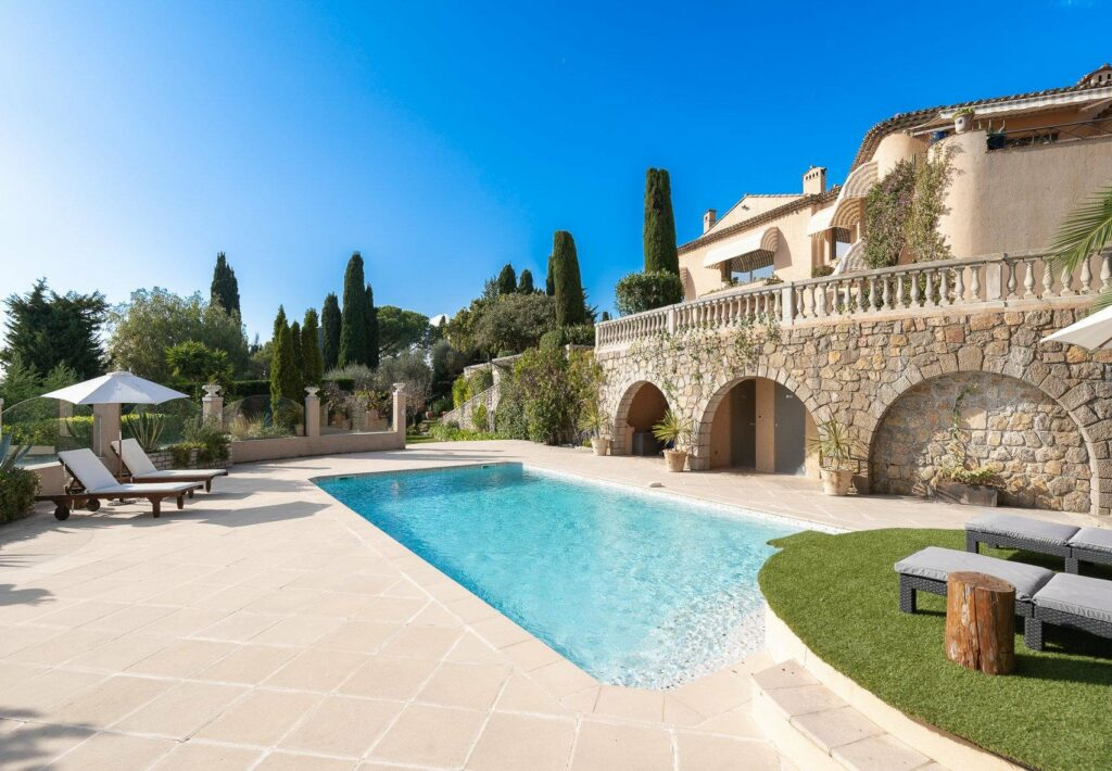 backyard of villa with large pool and surrounding tall trees