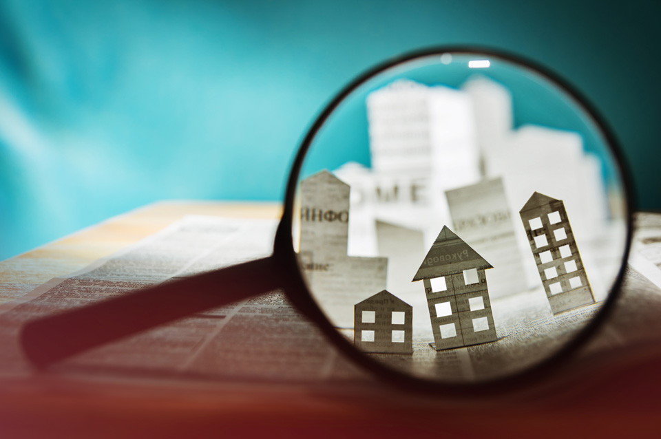 Magnifying glass in front of an open newspaper with paper home.