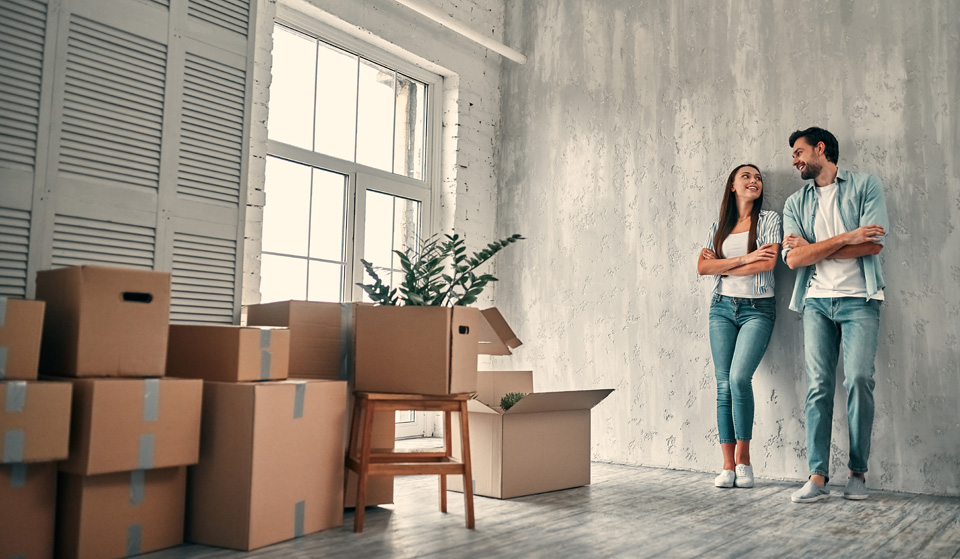 young woman and bearded man with cardboard moving boxes are happy to rent new property.
